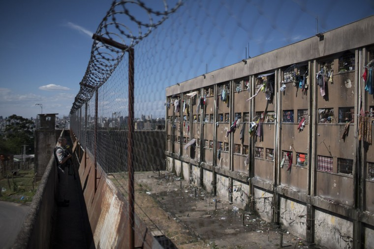 In this Nov. 30, 2015 photo, a police officer stands guard outside the Central Prison in Porto Alegre, Brazil. Police say they intercept at least 80 percent of what is thrown over the walls. The remaining 20 percent ends up in the hands of the prison gangs. (AP Photo/Felipe Dana)