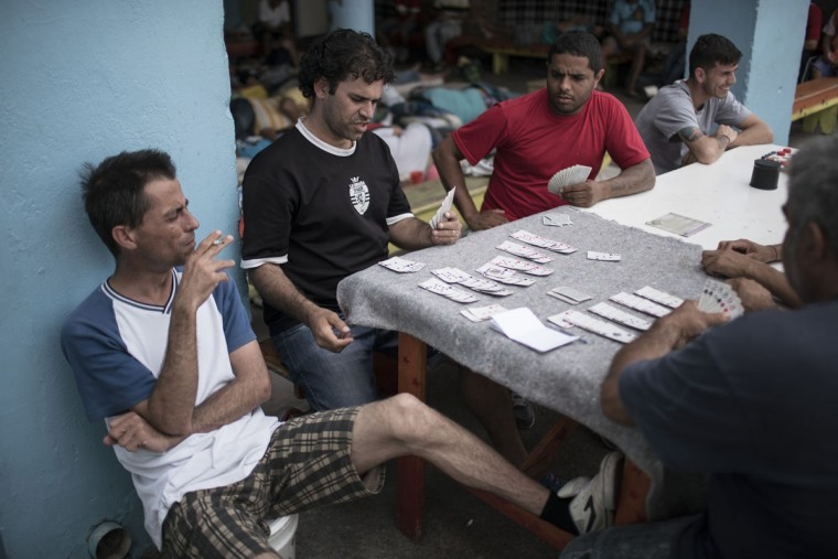 In this Dec. 1, 2015 photo, inmates play cards inside the patio of a cell block reserved for prisoners taking part in a work program at the Central Prison in Porto Alegre, Brazil. Inmates on work programs, voluntarily detoxing from drugs or from the LGBT community who are at high risk of being attacked, live in separate areas of the prison, but their special protection is unquestionably an exception. (AP Photo/Felipe Dana)