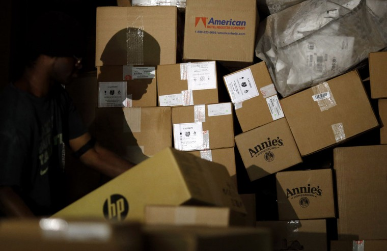 A worker's shadow is cast against boxes as he unloads them from a truck trailer at Worldport in Louisville, Ky. UPS and FedEx have been working with major retailers to hone their forecasts and have tailored their extra holiday workers to better meet the shipping spikes right after Thanksgiving and the weekend before Christmas. (AP Photo/Patrick Semansky)