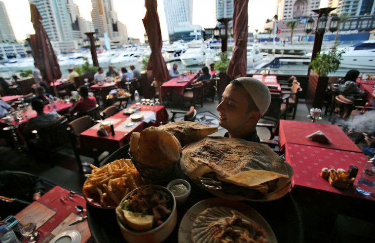 A waiter carries a tray of traditional Arabic food at a restaurant by the water canal at the Marina district, in Dubai, United Arab Emirates. Surrounding the Marinaís canal is an oasis of trendy restaurants and bars that serve an array of fusion-style cuisines that reflect the myriad of cultures and people drawn to Dubai, a modern city-state where foreigners far outnumber the locals. (AP Photo/Kamran Jebreili)