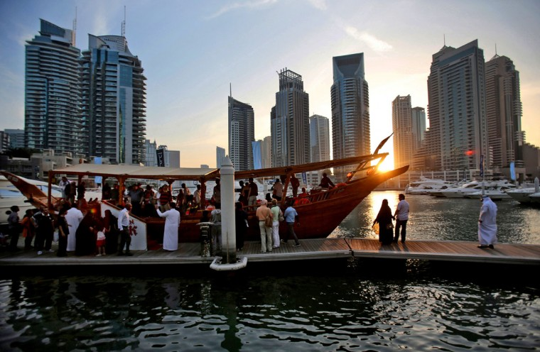 Tourists of different nationalities board a dhow for a cruise as the sun sets in the Marina neighborhood of Dubai, United Arab Emirates. Dubaiís year-round sunshine gives the Marina a summer-vibe throughout the winter months, when temperatures rarely drop below a comfortable 75 degrees Fahrenheit (24 Celsius) during the day. (AP Photo/Kamran Jebreili)