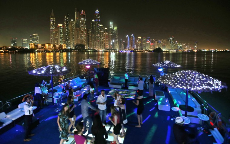 Guests dance on the GuGu boat during a private party opposite the skyline of the Marina Waterfront in Dubai, United Arab Emirates. Dubaiís year-round sunshine gives Marina a summer-vibe throughout the winter months, when temperatures rarely drop below a comfortable 75 degrees Fahrenheit (24 Celsius) during the day. On weekends, alcohol-fueled party boats ferry Russian and Western expatriates down the canal as speed boats and jet skis come out for a ride. (AP Photo/Kamran Jebreili)