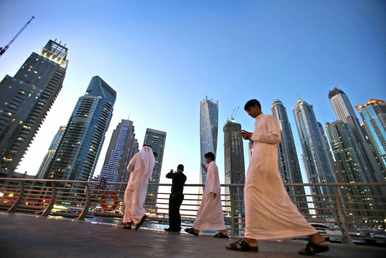 "Gulf Arab visitors in their traditional ""Kandora"" pass by giant skyscrapers at the Marina waterfront in Dubai, United Arab Emirates. The area is sometimes referred to as the Manhattan of the Middle East and some of its buildings are promoted by realtors as having ìManhattan styleî architecture. Penthouses in the Dubai Marina are similarly priced to New York Cityís upscale properties. (AP Photo/Kamran Jebreili)"