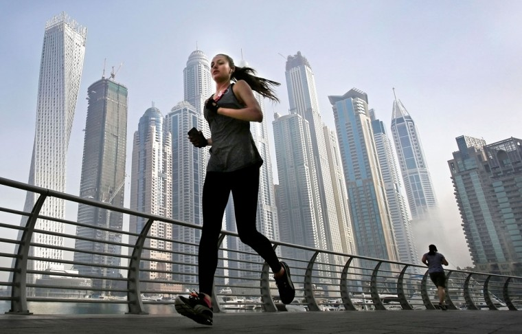 As the early morning fog lifts, a woman jogs in front of giant skyscrapers at the Marina waterfront in Dubai, United Arab Emirates. Dubaiís rapid transformation from a desert outpost into one of the worldís most architecturally stunning cities is mapped out in Marina. Where just 15 years ago there was empty, flat land, today a bustling neighborhood thrives centered around a canal and an impressive skyline. (AP Photo/Kamran Jebreili)