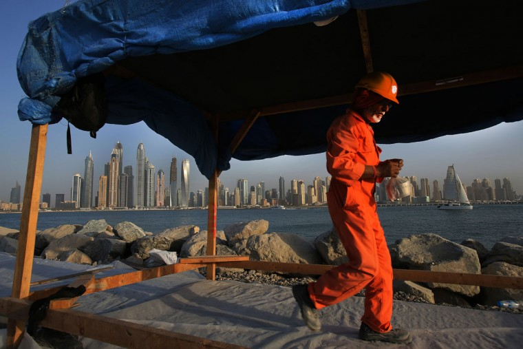 A laborer carries his lunchbox as he leaves a construction site for the day at the Palm Jumeirah opposite the Marina district, in Dubai, United Arab Emirates. Armies of low-paid migrant workers, many of them from the Indian Subcontinent, leave behind families and travel to Dubai to build soaring towers like those in the Marina. While the wages they come for offer hope of a better life, they are far too meager for most to ever dream of calling the Marina they built home. (AP Photo/Kamran Jebreili)