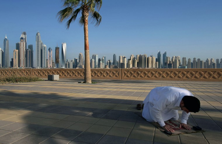 In this April 6, 2015 photo, with the Marina skyline as a backdrop, a Muslim man performs the afternoon prayer on Jumeirah Palm Island's walkway, in Dubai, United Arab Emirates. High-rise buildings, stacked row after row, make up this 50 million sq. foot (4.65 million sq .meter) waterfront neighborhood that is built around a man-made canal where the wealthy park their yachts. To mark its place in the world, the Dubai Marina boasts the world''s tallest residential building. (AP Photo/Kamran Jebreili)