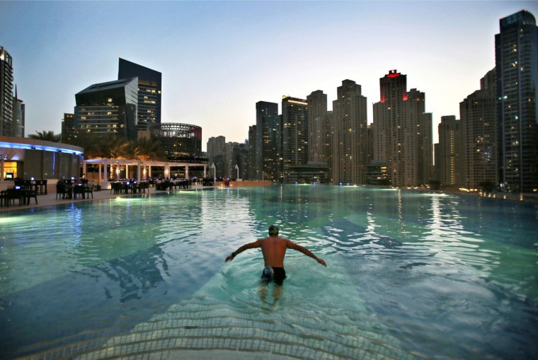 In this April 12, 2015 photo, a man dives into a hotel pool in the Marina neighborhood of Dubai, United Arab Emirates. The Marina is one of many clusters of neck-bending skyscrapers built throughout Dubai, but its real power lies behind the gated privacy of its most luxurious towers. Owning an apartment in one of these towers means access to skyline pools, concierge services and grand apartments that cater to the region''s royalty, as well as the world''s wealthiest businessmen and women. (AP Photo/Kamran Jebreili)