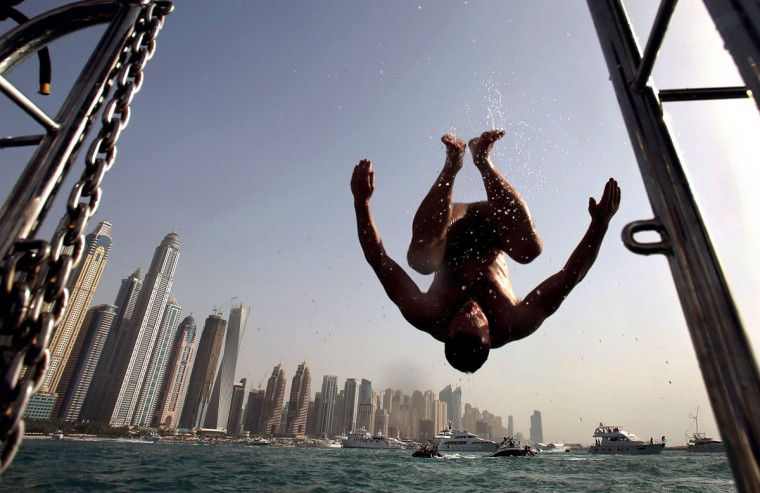 In this April 24, 2015 photo, a man does a flip into the water opposite the Marina Waterfront skyline in Dubai, United Arab Emirates. Dubai''s year-round sunshine gives Marina a summer-vibe throughout the winter months, when temperatures rarely drop below a comfortable 75 degrees Fahrenheit (24 Celsius) during the day. (AP Photo/Kamran Jebreili)