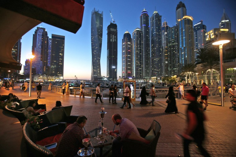 In this May 1, 2015 photo, two men play backgammon while smoking a shisha, or water pipe, at a restaurant overlooking the canal and the Marina neighborhood. Surrounding Marina's canal is an oasis of trendy restaurants and bars that serve an array of fusion-style cuisines that reflect the myriad of cultures and people drawn to Dubai, a modern city-state in the United Arab Emirates where foreigners far outnumber the locals. (AP Photo/Kamran Jebreili)