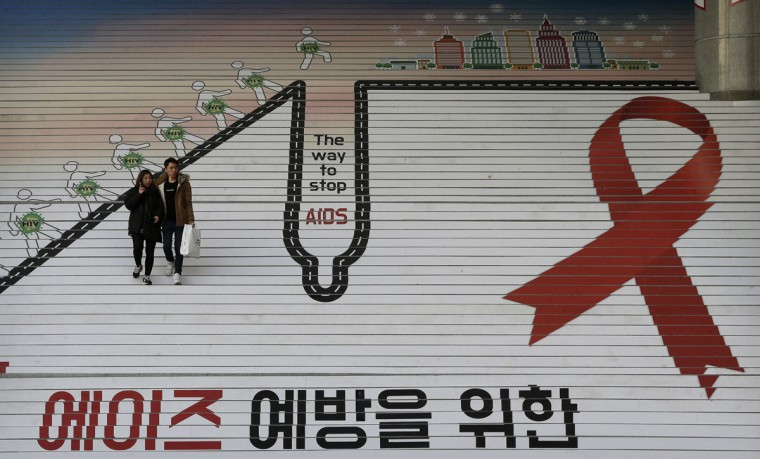 "A couple passes by the red ribbon, the international symbol for AIDS awareness, on the stairs during a campaign to mark World AIDS Day in Seoul, South Korea, Tuesday, Dec. 1, 2015. World AIDS Day is observed on Dec. 1 every year to increase awareness about the AIDS. The letters read "" A campaign for the prevention of AIDS"" (AP Photo/Ahn Young-joon)"