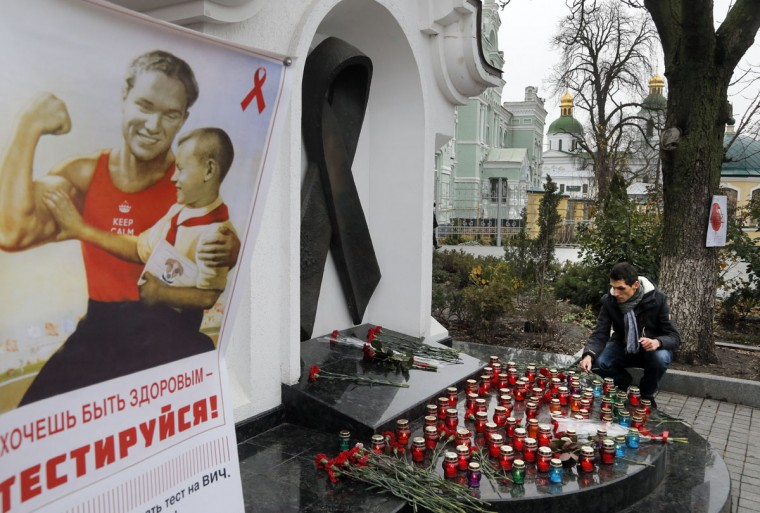 A man lays flowers at the memorial monument to AIDS victims to mark the 'World AIDS Day' and in memory of those who have died of AIDS in Kiev, Ukraine, Tuesday, Dec. 1, 2015. The poster with text that reads 'Do you want to be healthy- take the test'. (AP Photo/Efrem Lukatsky)