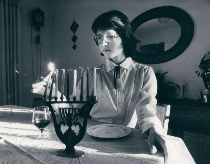 Ann Tsitlik, 12, lights a menorah. (Irving H. Phillips, Jr./Baltimore Sun, 1982)