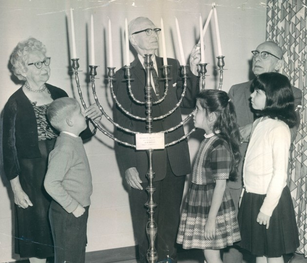 Irwin Spittell lights the Hanukkah candles of the large menorah in the lobby of the Jewish Community Center. (Edward Nolan/Baltimore Sun, 1964)