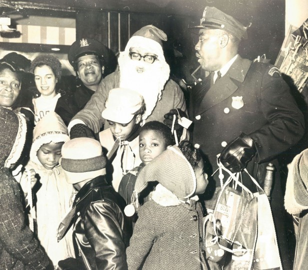 "Children in the Western Police District gather around Santa at the annual Christmas party at the Royal Theater. Patrolman Nathaniel Ponder, of the Western District, helps distribute stockings filled with ""goodies"" as the children leave. (Baltimore Sun, 1962)"