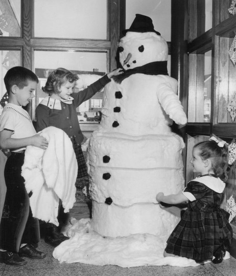 In 1953, a white Christmas didn't seem very likely so first-grade pupils at the Northwood Elementary School did some improvising. Here Billy Black, Judy Stryker and Linda Dave put the finishing touches to a fat snowman they built in a hallway of the school. Made of cotton, he boasts a carrot nose, hat and scarf. (Baltimore Sun)