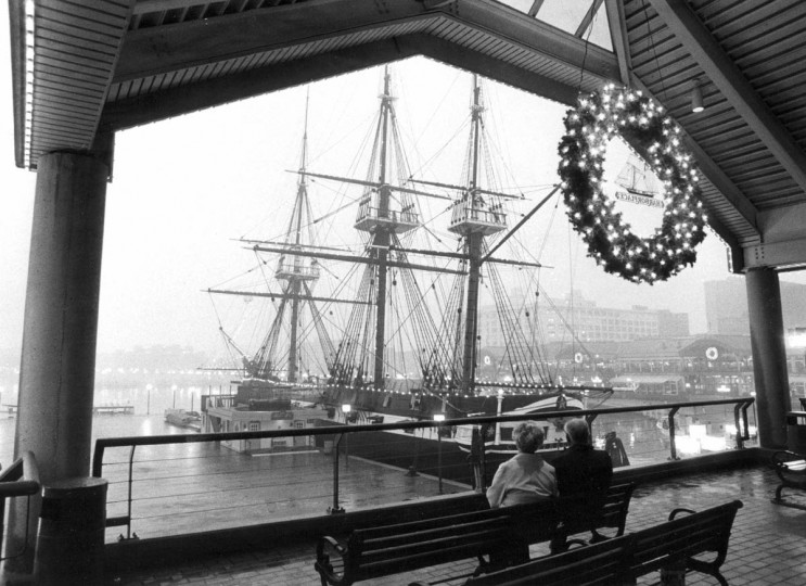From the masts of the U.S. Frigate Constellation to the pavilions of Harborplace and the downtown waterfront were adorned with Christmas finery in 1982. For this couple taking a break from holiday shopping, a promenade at the Pratt Street pavilion offered the best view. (Paul Hutchins/Baltimore Sun)