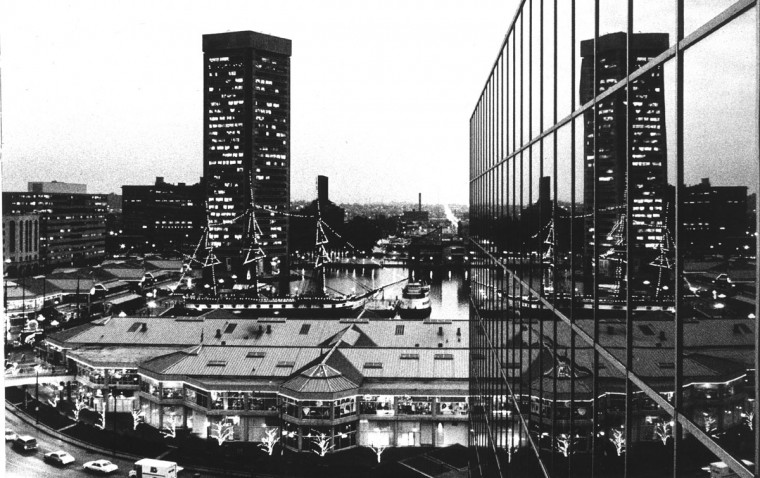As dusk approaches, the Inner Harbor goes up in lights. Here, the coming night and following illumination is seen reflected in the glass walls along the 12th floor of the Hyatt Regency hotel. The Christmas lights in the trees along Light Street provide the only clue that this is a winter scene. (Richard Childress/Baltimore Sun, 1982)