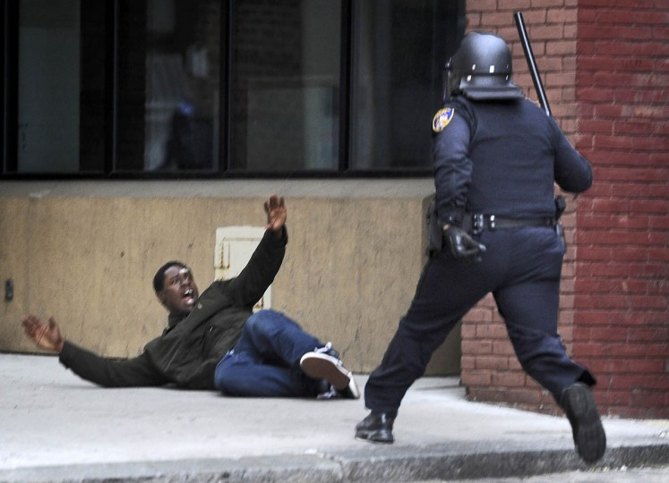 A Baltimore police man approaches a man near Lexington Market before arresting him. (Christopher T. Assaf, Baltimore Sun)