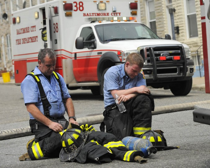 Two firefighters cool off after fighting a two alarm fire at 3521 E. Lombard Street. (Lloyd Fox/Baltimore Sun)