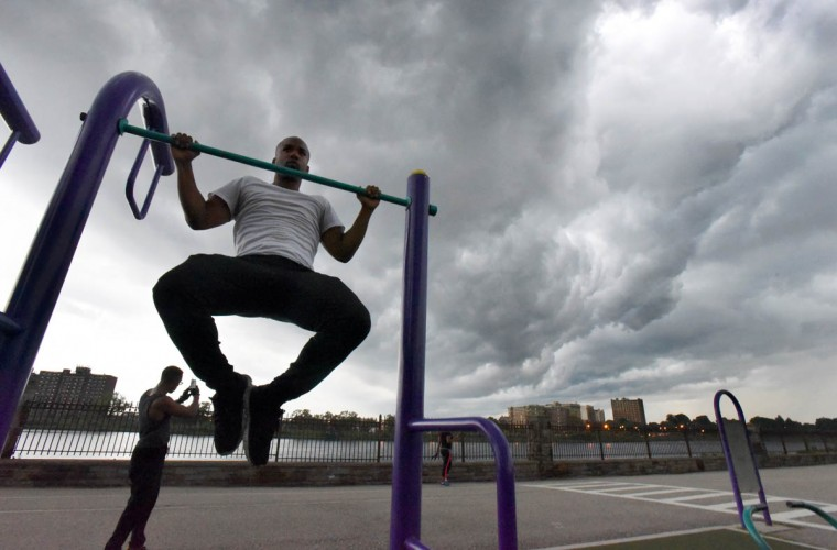 Josh Wofford, of Baltimore, works out at Druid Hill Park as storm clouds roll in on Thursday evening. (Jerry Jackson/Baltimore Sun)