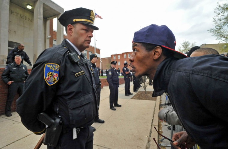 An unidentified man at right challenges one of the Baltimore City police officers, C. A. Thompson, as they stood in a line behind a barricade in front of the Western District police station Thursday evening. Protests have been held all week after Freddie Gray died in police custody on April 19. (Amy Davis, Baltimore Sun)