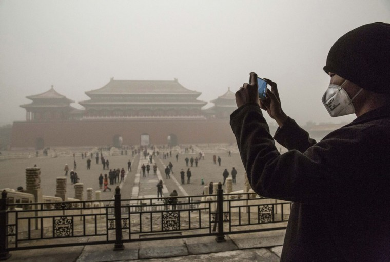 A Chinese man wears a mask as protection from the pollution as he takes a picture in the Forbidden City during a day of high pollution on December 1, 2015 in Beijing, China. (Photo by Kevin Frayer/Getty Images)