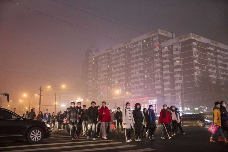 Chinese commuters cross a road on a day of high pollution on December 1, 2015 in Beijing, China. (Photo by Kevin Frayer/Getty Images)