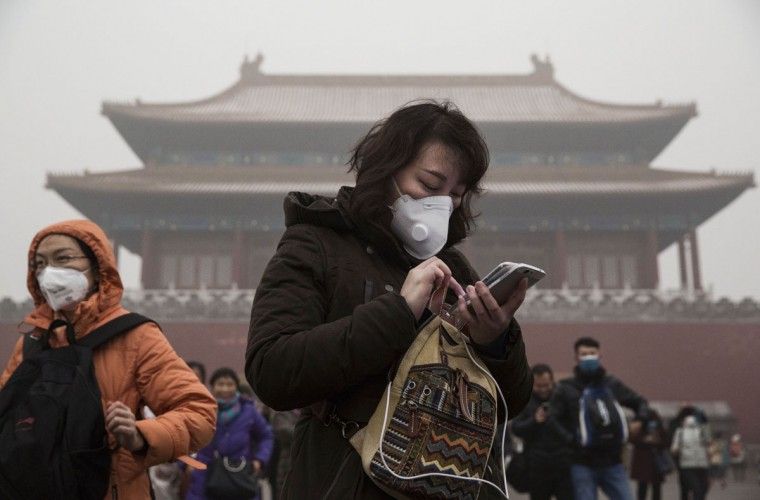 A Chinese woman wears a mask as protection from the pollution outside the Forbidden City during a day of high pollution on December 1, 2015 in Beijing, China. (Photo by Kevin Frayer/Getty Images)