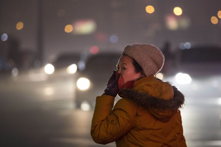A Chinese woman covers her face from pollution as she waits to cross a road on December 1, 2015 in Beijing, China. (Photo by Kevin Frayer/Getty Images)