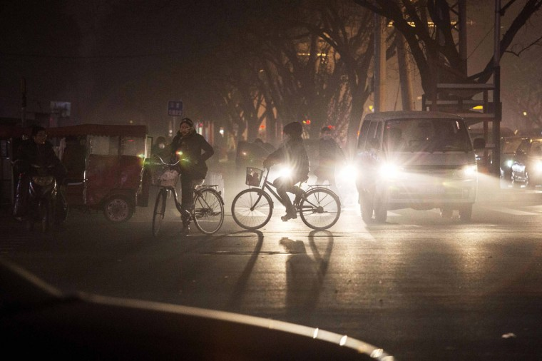Commuters ride bicycles in smog during a day of high pollution on December 1, 2015 in Beijing, China. (Photo by Kevin Frayer/Getty Images)