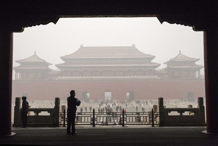 A Chinese man wears a mask as protection from the pollution as he stands in the Forbidden City during a day of high pollution on December 1, 2015 in Beijing, China. (Photo by Kevin Frayer/Getty Images)