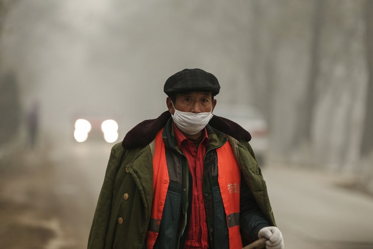 A Chinese worker wearing a mask on a day of heavy pollution on December 1, 2015 in Beijing, China. China's capital and many cities in the northern part of the country recorded the worst smog of the year with air quality devices in some areas unable to read such high levels of pollutants. Levels of PM 2.5, considered the most hazardous, crossed 600 units in Beijing, nearly 25 times the acceptable standard set by the World Health Organization. The governments of more than 190 countries are meeting in Paris this week to set targets on reducing carbon emissions in an attempt to forge a new global agreement on climate change. (Photo by Lintao Zhang/Getty Images)