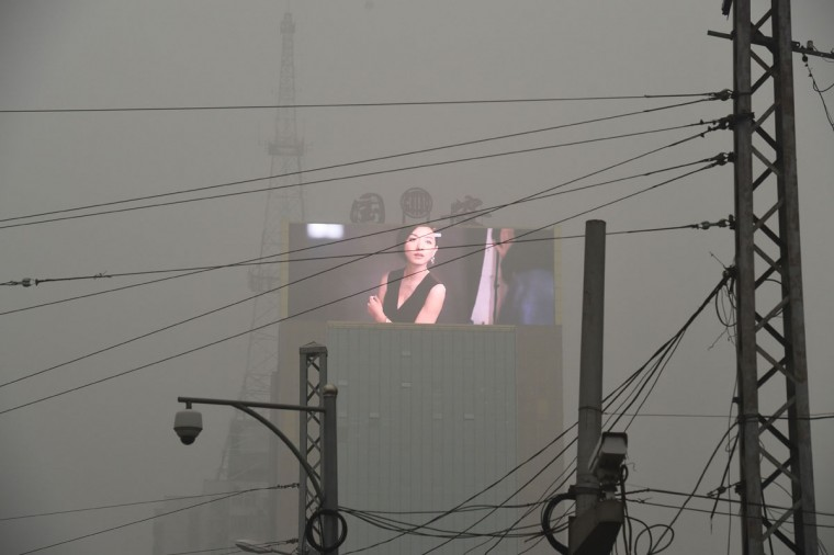 An electronic screen is seen through pollution in Beijing on December 1, 2015. China has ordered thousands of factories to shut as it grapples with swathes of choking smog that were nearly 24 times safe levels on December 1, casting a shadow over the country's participation in Paris climate talks. (GREG BAKER/AFP/Getty Images)