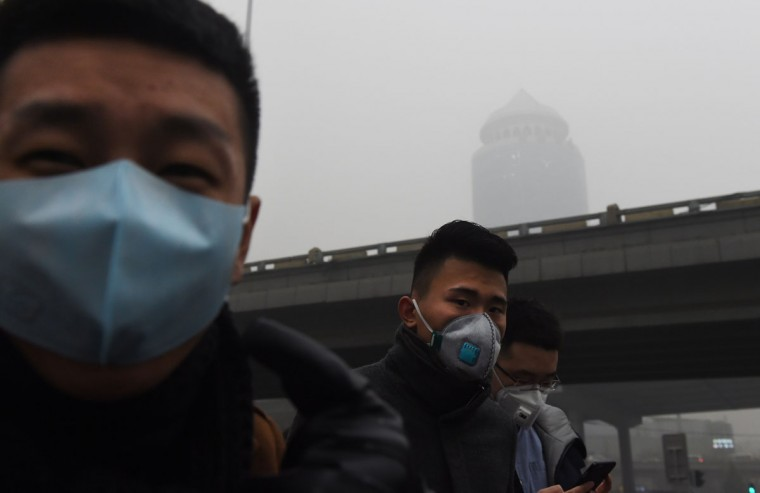 Pedestrians wear masks on a heavily polluted day in Beijing on December 1, 2015. (GREG BAKER/AFP/Getty Images)