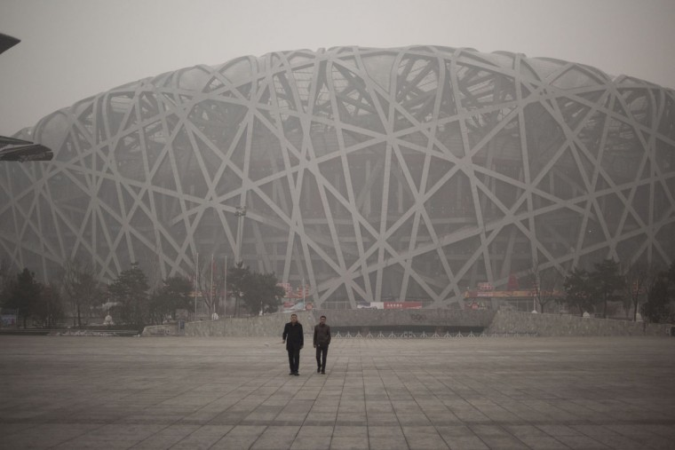 People visit the National Bird Nest stadium on a polluted day in Beijing on December 1, 2015. (FRED DUFOUR/AFP/Getty Images)