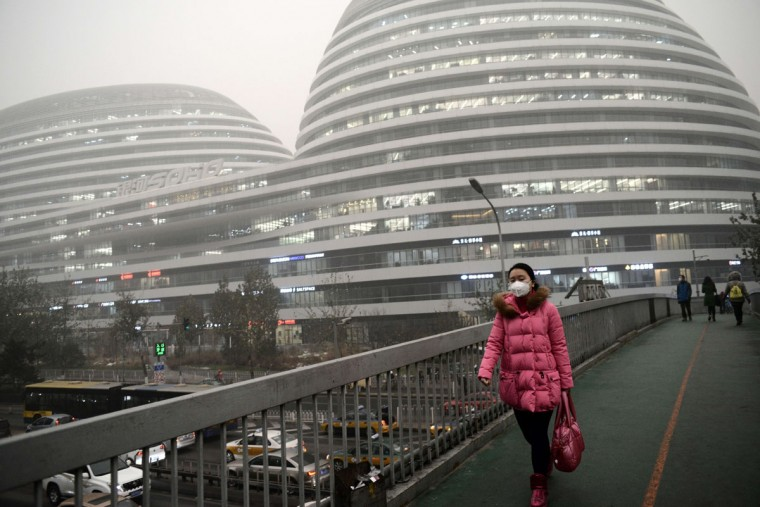 Pedestrians walk across a bridge in Beijing on December 1, 2015. China has ordered thousands of factories to shut as it grapples with swathes of choking smog that were nearly 24 times safe levels, casting a shadow over the country's participation in Paris climate talks. (CHAI HIN/AFP/Getty Images)