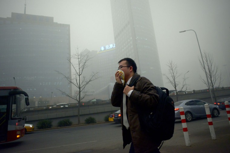 A man wearing a mask walks along a road in heavy pollution in Beijing on December 1, 2015. (WANG ZHAO/AFP/Getty Images)