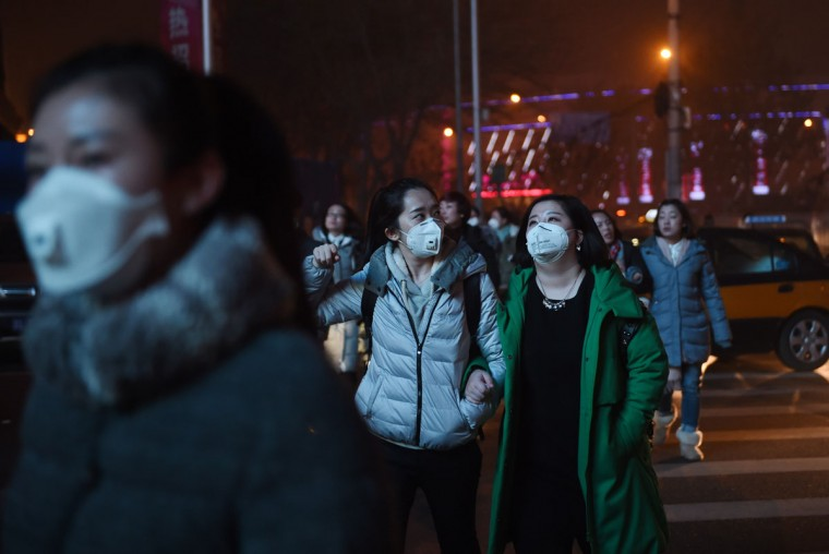 Pedestrians cross a road on a heavily polluted evening in Beijing on December 1, 2015. (GREG BAKER/AFP/Getty Images)