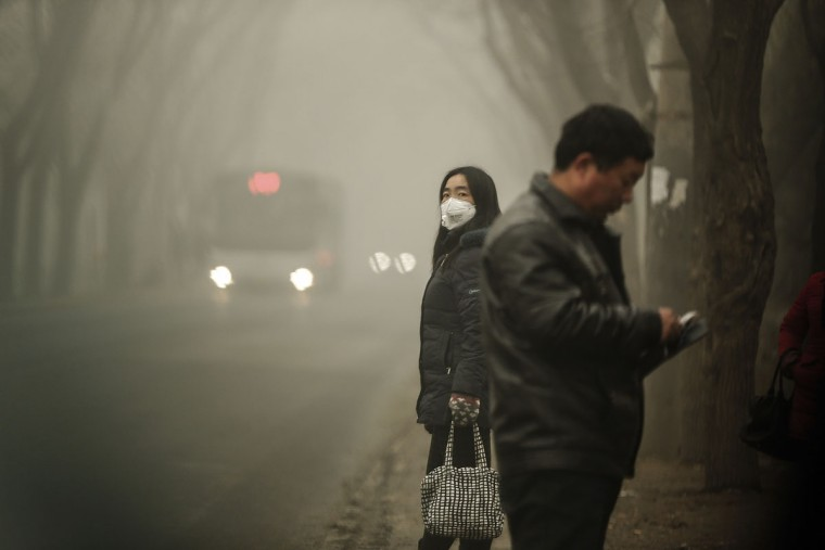 A woman wears a face mask next to traffic shrouded in heavy smog on December 1, 2015 in Beijing, China. (Photo by Lintao Zhang/Getty Images)