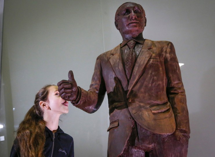 A girl tries to lick a chocolate statue of Russian President Vladimir Putin during the Chocolate Festival in St.Petersburg, Russia, Saturday, Dec. 5, 2015. The life-sized chocolate sculpture was created by Russian sculptor Nikita Gusev.(AP Photo/Dmitry Lovetsky)