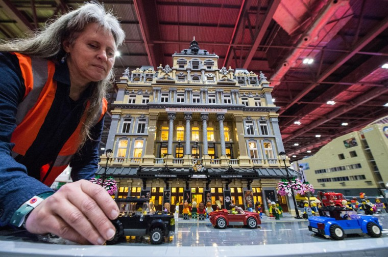 Lego builder Jessica Farrell finishes the street scene outside her Lego Her Majesties Theatre, with a performance of Phantom of the Opera taking place inside, made out of 57,992 bricks over 11 months at ExCel on December 10, 2015 in London, England. (Photo by Chris Ratcliffe/Getty Images)