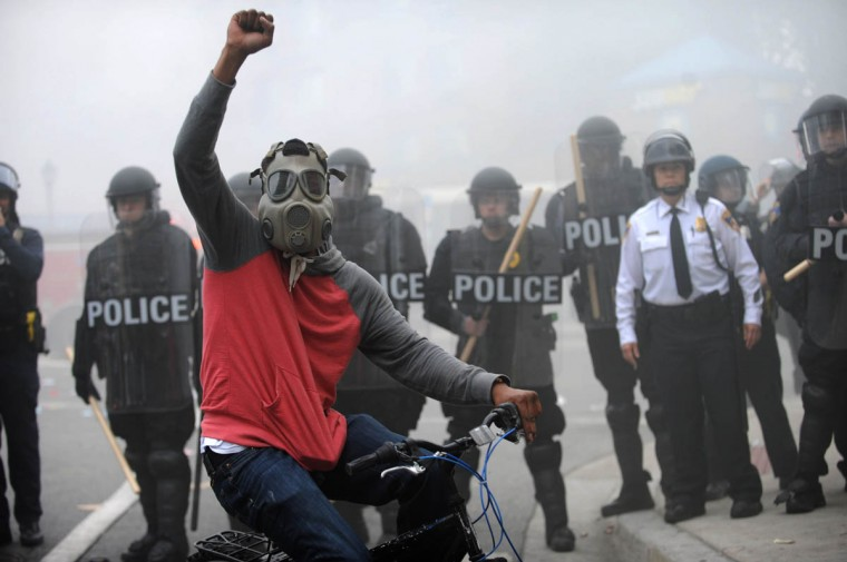 A protestor rides his bike in front of a police line at North and Pennsylvania Avenues on the day of Freddie Gray's funeral. Riots and looting broke out throughout the city. Gray died in police custody on April 19th. (Algerina Perna, Baltimore Sun)