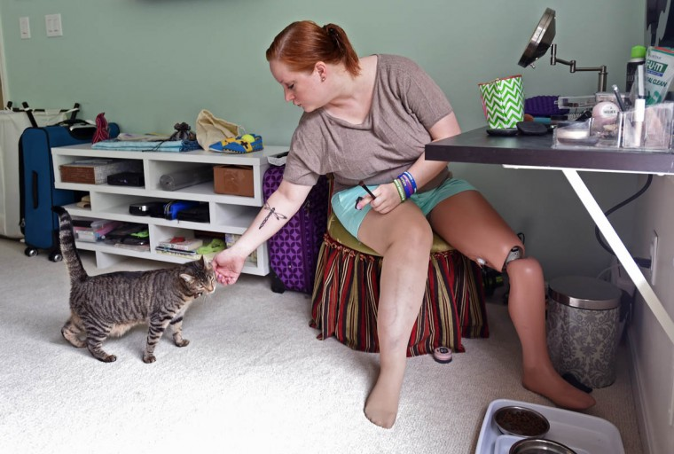 Erika Brannock plays with her cat Fenway Israel as she put on make up. Brannock, who lost her left leg during the Boston Marathon bombing, has moved on with her life while continuing to recover from her injuries. (Kenneth K. Lam/Baltimore Sun)