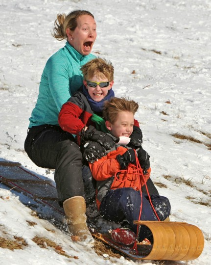 Kim Franklin, left, zips downhill with sons Connor, 8, center, and Matthew Franklin, 5, on a wooden toboggan the boys received for Christmas. Sledders enjoy the snow-covered hill in front of the Baltimore County Board of Education headquarters on North Charles Street. A wintry storm system heading north covered the Baltimore region with 3 to 5 inches overnight. (Amy Davis, Baltimore Sun)