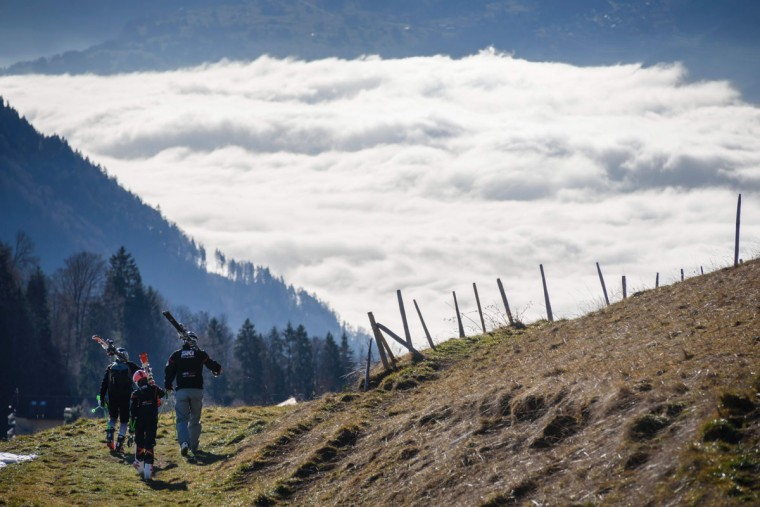 Tourists carrying their skis walk on a snowless hill back to the resort of Leysin, Swiss Alps, on December 28, 2015. (FABRICE COFFRINI/AFP/Getty Images)