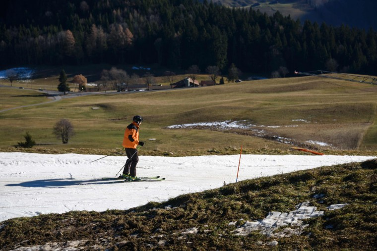 A tourist skis on a thin layer of snow near the resort of Leysin, Swiss Alps, on December 28, 2015. (FABRICE COFFRINI/AFP/Getty Images)