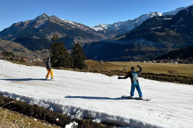 Tourists ski on a thin layer of snow back to the resort of Leysin, Swiss Alps, on December 28, 2015. (FABRICE COFFRINI/AFP/Getty Images)