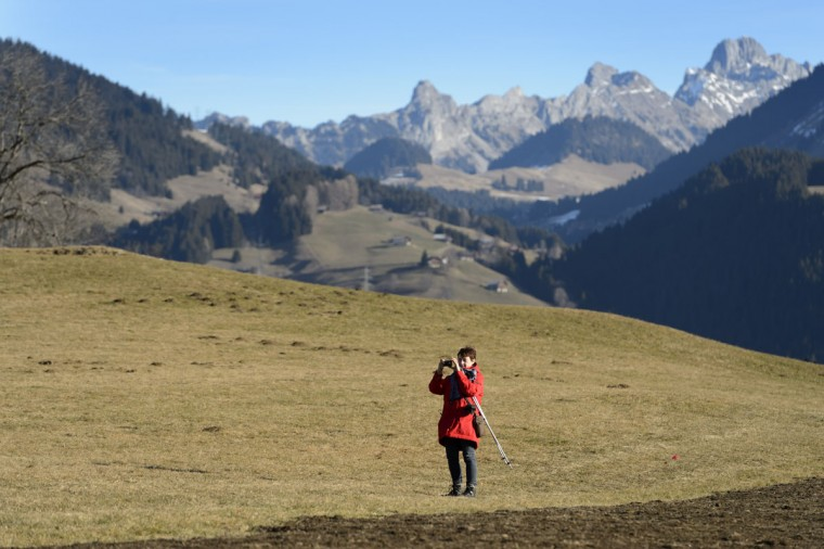 A woman takes a photograph as she walks on a green field without snow, in the Swiss Alps, during Christmas in Leysin, Switzerland, Thursday Dec. 24, 2015. The snow has melted as a result of the mild temperatures throughout the last few days. (Laurent Gillieron/Keystone via AP)