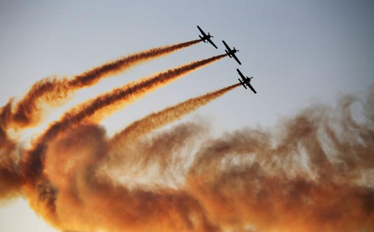 A team of aerobatics pilots perform a stunt at the World Air Games in Dubai, United Arab Emirates, on Sunday, Dec. 6, 2015. The World Air Games includes precision aerobatics, skydiving and hot air balloon competitions. (AP Photo/Jon Gambrell)