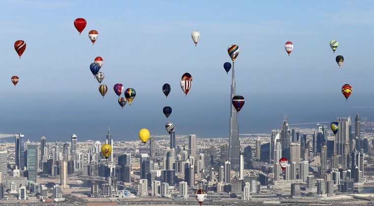 """Hot air balloons fly over Dubai during the World Air Games 2015, held under the rules of the Federation Aeronautique International (FAI) as part of the """"Dubai International Balloon Fiesta"""" event on December 9, 2015. (KARIM SAHIB/AFP/Getty Images)"""